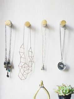 simple wooden wall pegs with gold tips with jewelry hanging from them. Cute & Functional: 5 DIY Projects That Look Good & Make Life Better