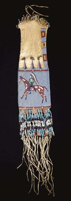 SIOUX PICTORIAL BEADED AND FRINGED HIDE TOBACCO BAG    composed of finely tanned hide decorated with yellow ochre, finely sinew-sewn in numerous colors of glass beadwork against a light blue ground, with equestrian figures on both sides, each wearing a traditional costume and feather bonnet, the broad beaded panels surmounted by triangles spot-stitched on the hide ground, trimmed with tin cone pendants, the lower section decorated with fringe,profusely strung with tu