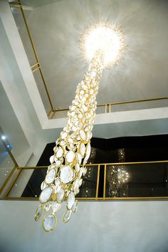 A breathtaking chandelier by French artist François Pascal hangs in the middle of the store. It's use of crystals is a nod to Coco Chanel and its importance to her. Coco Chanel Fashion, Gold Color Scheme, Italian Chandelier, First Perfume, All Of The Lights, Hanging Light Fixtures, French Artists, Diamond Are A Girls Best Friend, Lighting Design