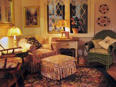 The living room features an easy chair and ottoman by Ruth Windheim, and a wicker chair and matching table by Pier 1/12. All the Windsor chairs in the house are by William Clinger, and all the rugs by McBay Miniatures. Lucy Pannute painted the end table. Plates are by Rosie Duck.