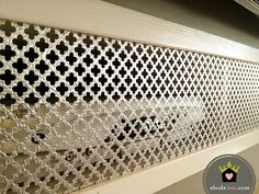 decorative sheet metal screen to hide cable boxes on a bookshelf