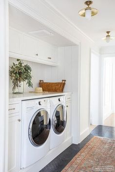 Shiplap trim frames a laundry room nook with a white front load washer and dryer in a cottage home design.