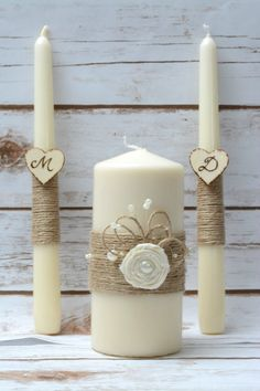 Rustic Wedding Set of 3 - Unity Candle Set , Knife Cake Set , Toasting Glasses  This listing is for set of 3 Rustic Unity Candle Set , Cake Cutting Set and Wedding glasses.  Please select the color of the roses!   ****************************** Ivory Rustic Unity Candle set for your ceremony  Set of 3 candles decorated with natural twine and the wooden hearts have been engraved with a wood burner. The Big Unity is decorated with ivory fabric rose flower ,pearls and twine rope.  Color : Ivory…