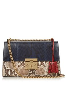 Gucci's fresh new Padlock bag is impeccably crafted from glossy python in shades of brown, red, and navy.