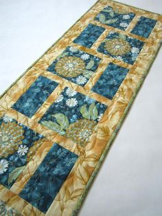 This table runner is stunning with the teal main color fabrics outlined by a gold leaf fabric. I beautiful runner that will look great in your room. Give this a