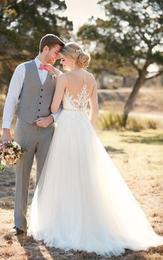 "This A-line wedding dress from Essense of Australia features an illusion lace bodice with glistening Diamante accents. The French tulle skirt falls gracefully to the floor into a romantic court train. The back zips up with ease under sparkling crystal buttons. Accent your waist with a 1/2"" beaded grosgrain belt."