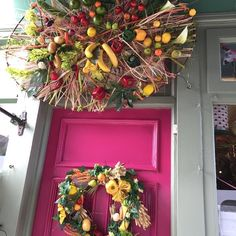 Fruits and vegetable oval sculpture above the shop door with door ring at our shop in Cowbridge