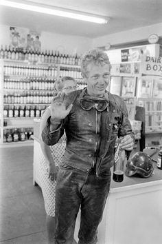 Steve McQueen in motorcycle gear making a pit stop for a soda pop. #MOTORCYCLE #BIKERS #MOTORCYCLEFEDERATION