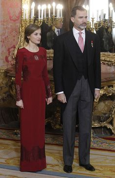 Glamorous Queen Letizia resplendent in a wine red figure-hugging gown with her husband King Felipe VI looked equally dapper in a smart suit as they welcomed the welcomed foreign diplomats to the royal palace in Madrid on Thursday January 26, 2017