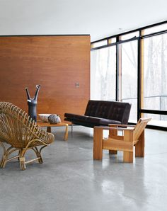 Architect William Massie built a hybrid prefab home for vintage retailer Greg Wooten, who handled the interiors. In the living room is a 1950s Franco Albini rattan chair, a Crate chair designed by Gerrit Rietveld in 1934, and a 1970s sofa by Edward Axel Roffman. The tall ceramic piece is by Bruno Gambone. Photo by Karina Tengberg.