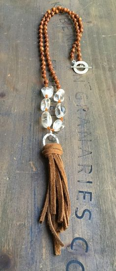 Beaded necklace with clear quartz and natural wood beads with leather tassel and toggle clasp