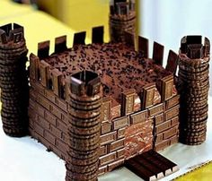 Its a chocolate castle. 2 square cakes on top of one another with icing, . cookies for the towers,( a wee bit of icing in between cookies for gluing them together ) chocolate bar pieces for brick . kit kat chocolate slab for Drawbridge. Chocolate Frosting, Chocolate Cookies, Vanilla Cookies, Torta Chocolate, Butterscotch Cookies, Twix Cookies, Making Chocolate, Chocolate Biscuits, Shortbread Cookies