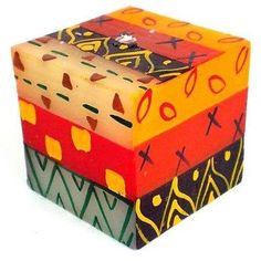 This colorful candle features a cube shape, which is hand-painted by artisans in South Africa. Each candle is 2.75 inches square.