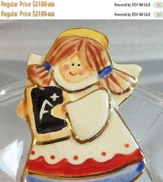 This #vintage porcelain angel teacher brooch is just fabulous!  It features a porcelain teacher angel in a red and blue pinafore with a white apron.  Her hair is in pigtails... #ecochic #etsy #jewelry #jewellery