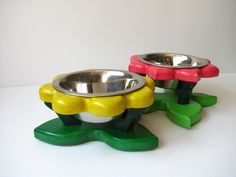 BROMELIADS This flower looking dog bowl stand is carefully handcrafted to details. The height of the stand is 9 cm and is free standing. This holder are for two bowls, all bowls are the same diameter 13 cm. . Quality stainless steel bowls are dishwasher safe.