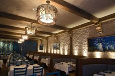 """Santorini Estiatorio is decorated in what the designer calls a """"rustic Greek island"""" look, with light colors and clean lines in the open, airy dining room."""