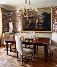In this dining room, the designers clad the walls in antiqued mirror hand-painted in a damask pattern | archdigest.com