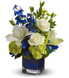 Wedding Flower Arrangements Serenade in Blue - A song for the eyes, this exquisitely lyrical bouquet in a chic contemporary glass cube vase is sure to impress anyone. Those with an eye for design are in for a special treat. Blue Flower Arrangements, Wedding Flower Arrangements, Floral Centerpieces, Flower Vases, Wedding Bouquets, Blue Wedding Centerpieces, Royal Blue Wedding Decorations, Table Arrangements, Centerpiece Ideas