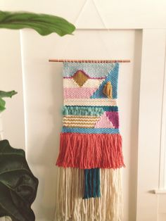 Woven Wall Hanging handmade on a lap loom using wool yarns, and wool roving. This weaving is very colorful with a lot of fun shapes! Small gold, and