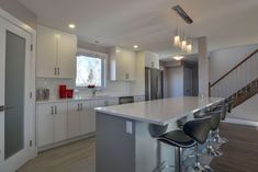 bright white kitchen with walk in pantry and breakfast bar island.