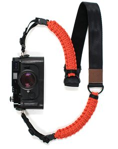 Originally used in the suspension lines of US parachutes during World War II, 550-lb test paracord flexes but will never break. Worn around your neck or as a sling, the strap's suspension shields your camera from shocks when you inattentively jump off rocks. The strap's sturdy nylon webbing with a suede lining wears soft against your sunburnt neck and easily supports the heaviest SLR and long-lens combos. *This model includes quick release.