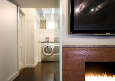 Copper penny tiles bring the fireplace alive with a metallic glint [Design: E/L STUDIO]