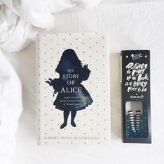 Livro The story of alice e marcador feito a mão inspirado na personagem Alice em uma cama branca.