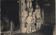 Nigeria, interior of building with Ibo sculpture. Represents small group of male and female adults and children Wearing cloths around lower bodies, head-gear. One figure standing on head of another. Section-view of adult male at left. Medium: Gelatin silver print.
