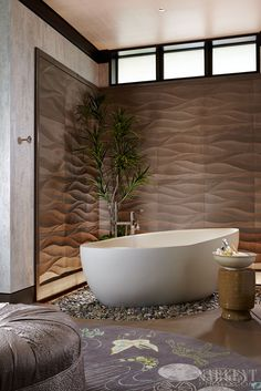 Contemporary Master bath, egg shaped stand alone tub resting on a bed of river rocks, accent wave stone wall tile accented with a wash of light. Asian inspired bathroom, custom lily pad round rug
