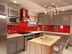 Saturated red walls in this kitchen by designer Meg Caswell are a real showstopper — but the intense hue isn't courtesy of a tile backsplash, instead Meg painted the walls red, then covered them with glass panels for added shine and ease in cleaning.
