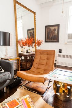 How To Mix High & Low Decor — Inside A Dreamy R29 Apartment #refinery29  http://www.refinery29.com/ashley-miles-home-tour#slide2  A set of leather chairs and a gold side table create a separation between the entryway and living room.