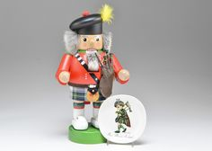 A polychromed wooden nutcracker figure, in the form of a Scottish highlander, with bag pipes and tartan kilt. Includes dish with transfer of child playing bagpipes. from EBTH.com