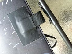 duct tape a loop of fabric or elastic to the inside of your notebook or journal---diy pen loop for notebook - journal
