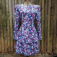 """Vintage 80s Floral Peplum Dress Long Sleeve Shoulder Pads.  To really experience the 1980s one must walk a mile in shoulder pads and a tiered peplum skirt. Attached ties for a big bow in the back. Back zipper for easy fit.   Details Size: """"10"""" fits like a 4 Chest: 34"""" Shoulders: 13.5"""" Waist: 28"""" Hips: 36"""" Length of skirt (from waistline): 18"""" Overall Length: 34""""  Brand: unmarked  Colors: black, white, lavender, fuschia, blue, green"""