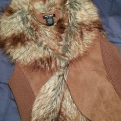 """100% Suede w/Faux Shearling Trim GORGEOUS real suede vest with ribbed cotton sides and full suede panel on front and back. Cozy chic faux shearling fur. Get your best suede boots and jeans on with this one ladies! underarm across to underarm (bust area) is 19"""", bottom across is 18"""", armpit to bottom is 18"""", top of shoulder across to shoulder is 18"""", and back top @ nape of neck to bottom is 21"""". Clothes by Revue Jackets & Coats Vests"""