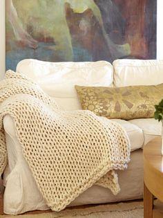 Et grovstrikket pledd og en gyllen pute gjør sofaen ekstra innbydende. Det store maleriet myker opp de hvite veggene. Styling: Tone Kroken.