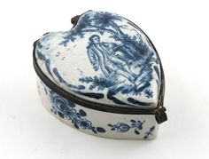 A small Dutch Delft heart-shaped snuff box 19th century, the metal-mounted hinged lid painted in blue with a gallant beneath a tree, the sides with flowers, AL monogram to the base