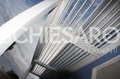 Pergolato in alluminio verniciato bianco, con apertura a lamelle orientabili, meccanismo di apertura motorizzato. Addossato a parete esistente.