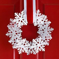 Rely on Color for Contrast: Wooden snowflake cutouts spray painted and glued on top of each other. Wide double ribbons one white, one less narrow red- adds a simple elegant finish.