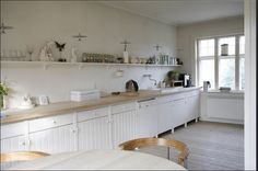 scandinavian kitchen, rustic cabin, white painted wood, light bleached wood floors, scandinavian wood stove, painted wood cabinets, open shelving