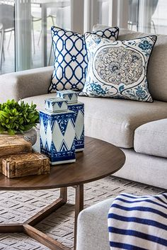 Gorgeous living room with a contemporary light gray sectional sofa layered with blue and white trellis patterned pillows, blue and white medallion pillow and a blue and white striped throw.