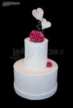 Torta nuziale multipiano con dettagli di fiori rosa e cuori