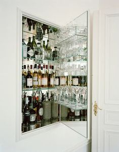 Fabulous hidden bar with mirrored interior and acrylic shelves lined with assorted glassware and liquor.
