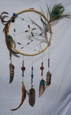 This handmade dream catcher is 30cm (12inch) in diameter, woven with hemp cord in an abstract form  It is adorn with Amethyst, turquoise, labradorite, blue aventurine, lapis lazuli, snowflake obsidian and shells As well as beautiful pheasant, coque, guinea fowl, duck tail, peacock eye and plumage. Also in the middle is a big Tree of life Pendant.   Please note this is handmade so there will be imperfections perfectly imperfect =)