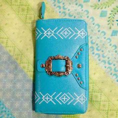 Turquoise Southwestern Wallet w Silver Buckle Turquoise Southwestern Wallet w/Buckle Trim. Brand new in original packaging.   Zip around style wallet, inside there is 2 bill slots (1 on each side of wallet), 8 card slots (4 on each side of wallet), center zipper compartment for change or whatever.  Made of faux leather, has southwestern design stitching on both sides, front has round silver colored rivets & a silver colored buckle (buckle is not functional it's just for decoration).  Faux…