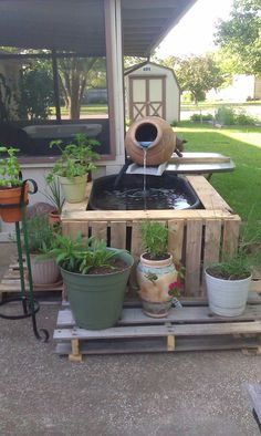 planters pot for fountain and pallets around pond.