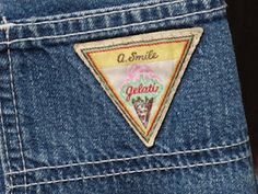 A. Smile Jeans with the ice cream logo!  I had about five pair of these in different colours, including green painter-style overalls!  4th grade, 1981-2.  These came in and went out so fast and I'm not sure why.