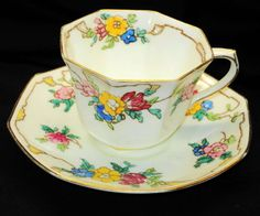 Doulton deco: unnamed tea duo on octagonal shape, H3960, c1931 (4). Blue, pink and yellow flowers linked by abstract branches and yellow patches, including to inner cup rim, with gold gilt highlights and trim.