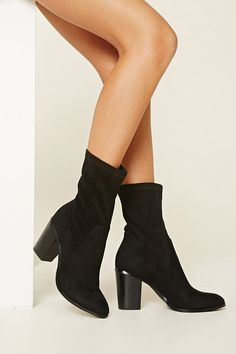 A pair of faux suede ankle booties featuring a faux wood block heel and a slightly pointed toe.