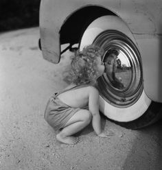.little girl sees her distorted reflection in the chrome rim of a car from somewhere between 1930s-1950s vehicle.